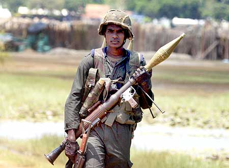 A Sri Lankan government soldier walks with his weapons near the town of Putumatalan located at the 'No Fire Zone' in northern Sri Lanka