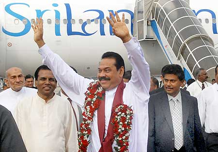 Sri Lankan President Mahinda Rajapaksa waves after disembarking his airplane at Colombo airport