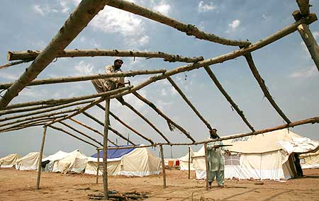 Men build a shelter, for those displaced by the military offensive in Swat, at a UN camp