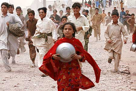 Children, fleeing a military offensive in the Swat valley, chase after food donations at a UN camp