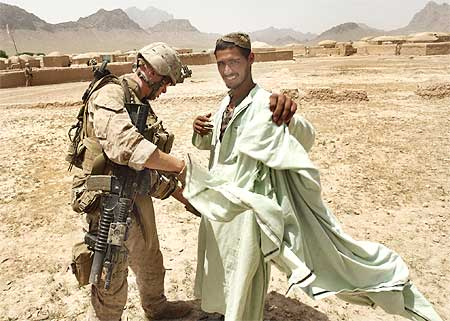 A US Marine searches a man for weapons in a village in Golestan district of Farah province