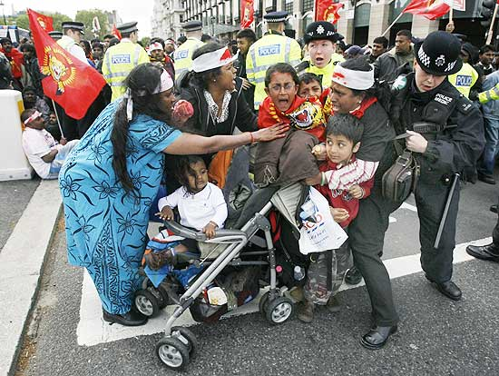 Pro-Tamil demonstrators scuffle with police after blocking a road in front of the Houses of Parliament in London