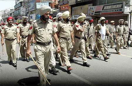 Policemen patrol a street in Amritsar