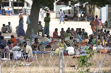 Tamil civilians sit behind a barbed-wire perimeter fence in a refugee camp in the northern Sri Lankan town of Vavuniya on May 26