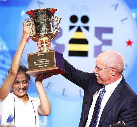 Kavya is presented the winner's trophy by President and CEO of the EW Scripps Company Richard Boehne