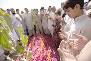 Family members pray over the grave of Sidra Khalid, who was killed in the Islamabad university blast