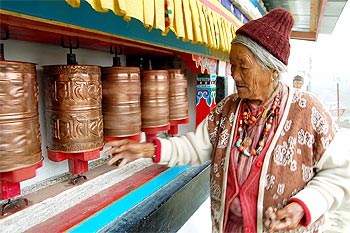An elderly lady of the Manpa tribe spins prayer wheels at a monastery in Tawang, Arunachal Pradesh