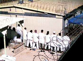 Detainees participate in a prayer session at Camp IV in Guantanamo Bay