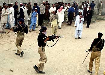Policemen try to control an unruly crowd in Pakistan.
