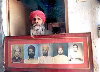 A file picture of a victim with a photograph of relatives lost in the 1984 riots.