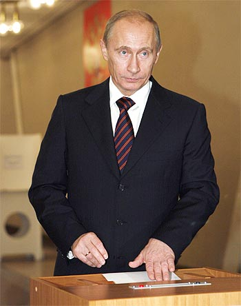 Russian Prime Minister Vladimir Putin drops his ballot into a ballot box at a polling station in Moscow.