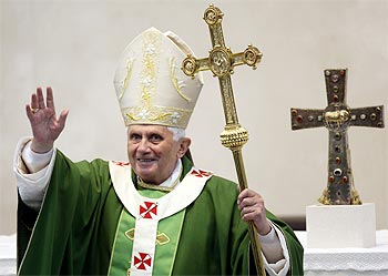 Pope Benedict XVI holds a cross as he waves after a mass in Brescia,Italy