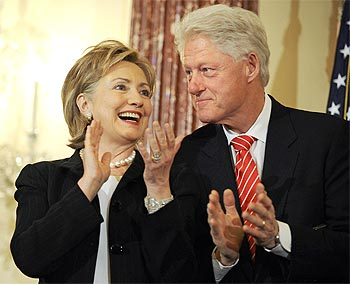 US Secretary of State Hillary Clinton (L) takes the stage, beside her husband former US President Bill Clinton.