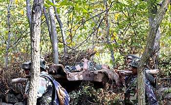 Soldiers carry an injured comrade on a makeshift stretcher through a jungle during a gun battle with militants in Noor Takiya, 25 km south of Srinagar