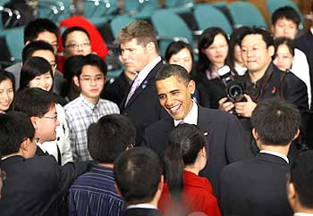 Obama greets participants at a town hall-style meeting with future Chinese leaders at Shanghai