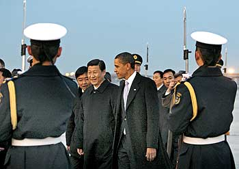 US President Barack Obama and Chinese Vice President Xi Jinping walk past an honour guard after Obama's arrival in Beijing