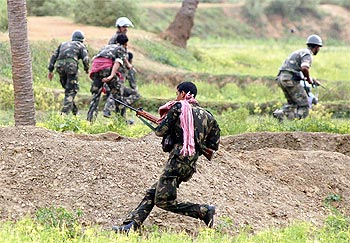 Paramilitary soldiers run for cover during a gunfight with Maoist rebels in Pirrakuli village near Lalgarh