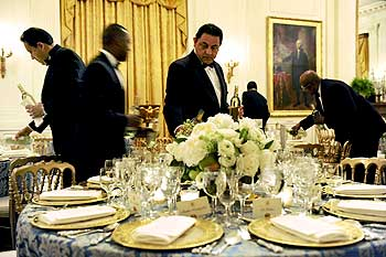 Waiters pour wine in the candle-lit East Room before US President Barack Obama plays host to congressional committee chairmen for a dinner at the White House
