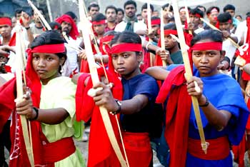 Naxals pose with bows and arrows during a rally in Kolkata