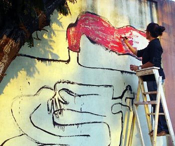 A participant paints the wall in tribute