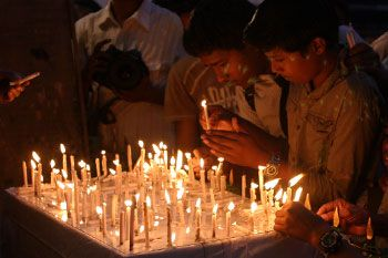 Children lighting candles outside Chabad house