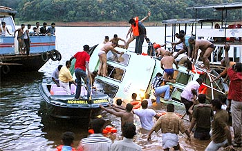 Rescue workers stand over the capsized boat on Periyar lake in Thekkady on Wednesday