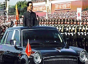 A giant screen shows China's President Hu Jintao reviewing soldiers at the parade