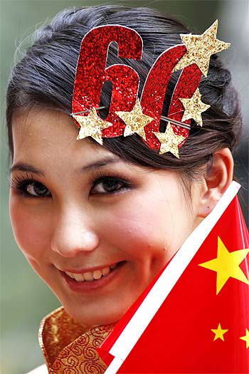 A model holds a national flag of China outside a shopping mall in Beijing