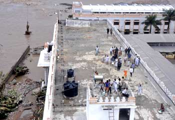 Flood-affected people stand on top of a building in the flooded areas of Mantralaya district of Andhra Pradesh