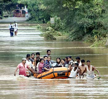 People use a rescue raft as they wade through floodwaters
