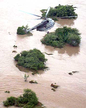 An IAF rescue team member prepares to lift a flood victim from a flooded area