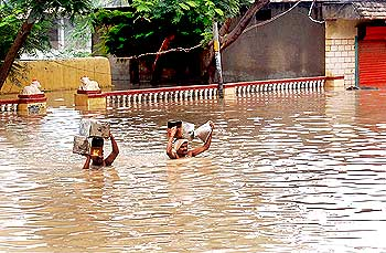 Residents of Kamatagi, Bagalkot district walk through flooded street due to heavy rain