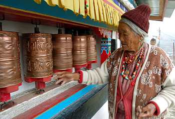 An elderly woman belonging to the Manpa tribe spins the prayer wheels at a monastery in Tawang