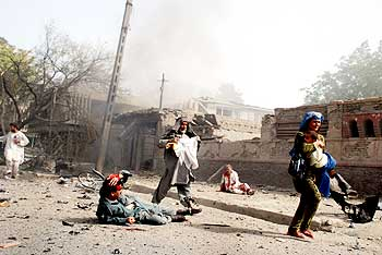 Locals flee the scene of suicide attack on the Indian embassy in Kabul on July 7, 2008