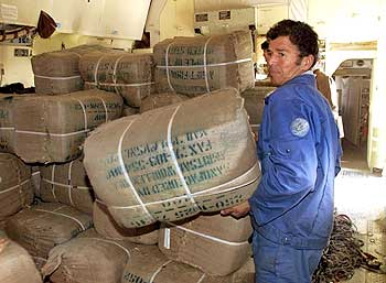 A worker with blankets delivered from India as he unloads a plane in Termez, on the Uzbegistan-Afgha