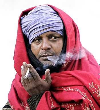 A man smoking a bidi.