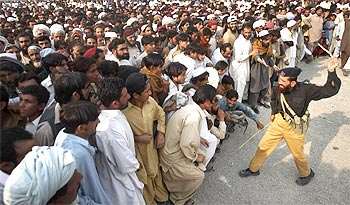A policeman threatens to strike a man, who was fleeing a military offensive in South Waziristan, for jumping a queue at a food distribution point