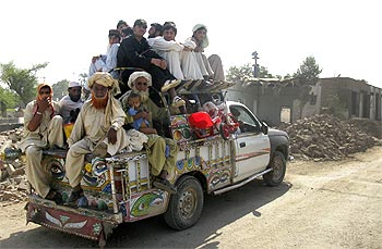 Residents fleeing the military offensive against Taliban in South Waziristan pack a vehicle while going through Bannu