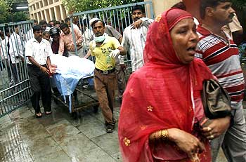 A hospital worker and relatives bring out the body of Lalita, a schoolgirl who died in the stampede