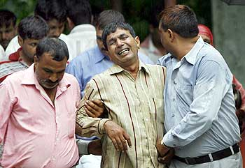 Nawab Singh Nagar (centre), Lalita's father, is consoled by relatives