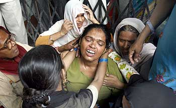 Relatives console Shamsiran Begum (centre), mother of Afroz, a school girl killed in the stampede.