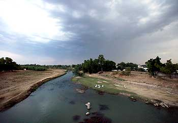 Men sit along a river running through Mardan district
