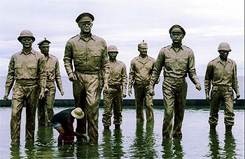 A Filipino worker cleans General MacArthur's statue