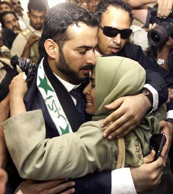 Muntazer al-Zaidi embraces his sister upon arrival at the Al-Baghdadya television station following his release from prison in Baghdad