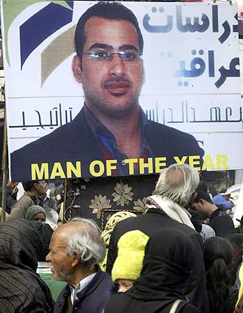 People walk past poster of Iraqi journalist al-Zaidi