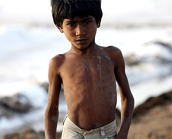 A worker's son poses for a picture at a salt pan near Bhavnagar in Gujarat