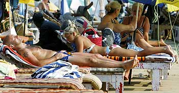 Tourists relax at the Baga beach in Goa