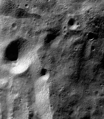 An image of the moon's surface, taken from the lunar orbit by Chandrayaan-1 spacecraft's Terrain Mapping Camera, shows many large and numerous small craters. The bright terrain on the lower left is the rim of the 117-km wide Moretus crater.