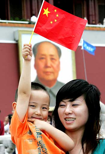 Tourists pose for a picture alongside a Mao portrait close to Tiananmen Square in Beijing