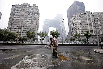 A worker sweeps water off a Beijing street